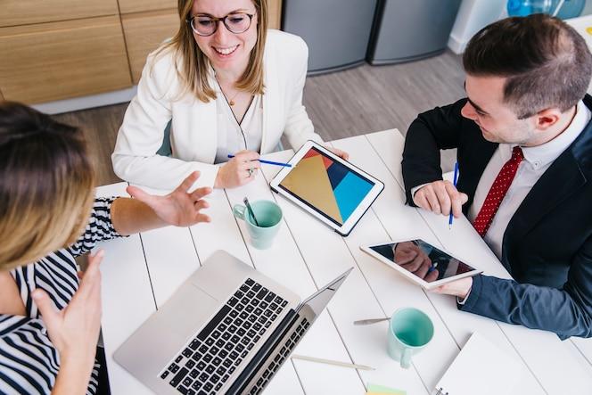 Compañeros amistosos con dispositivos en el escritorio