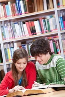 Compañeros de clase compartiendo libros en la biblioteca