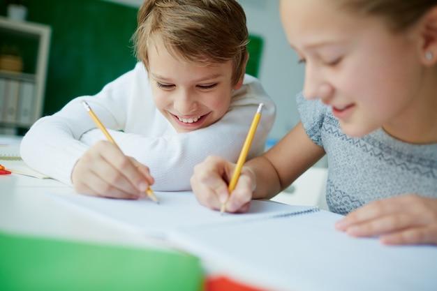 Compañeros de clase escribiendo en el mismo cuaderno
