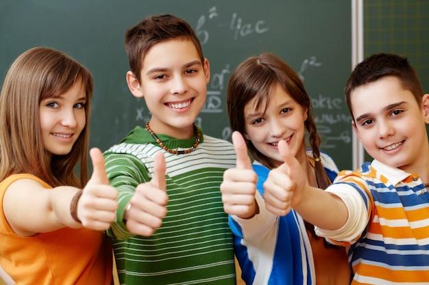 Compañeros de clase con el pulgar hacia arriba en un aula