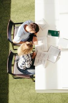 Compañeros de clase sentados en la biblioteca juntos