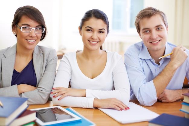 Compañeros de clase sonrientes trabajando juntos