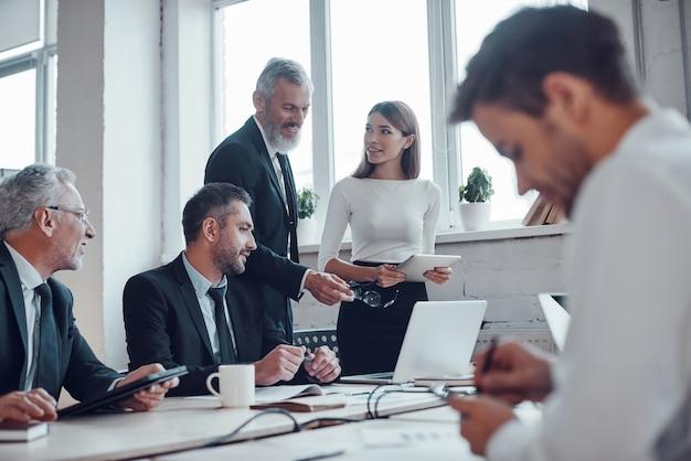 Compañeros confiados discutiendo el próximo paso comercial mientras trabajan juntos en la oficina moderna