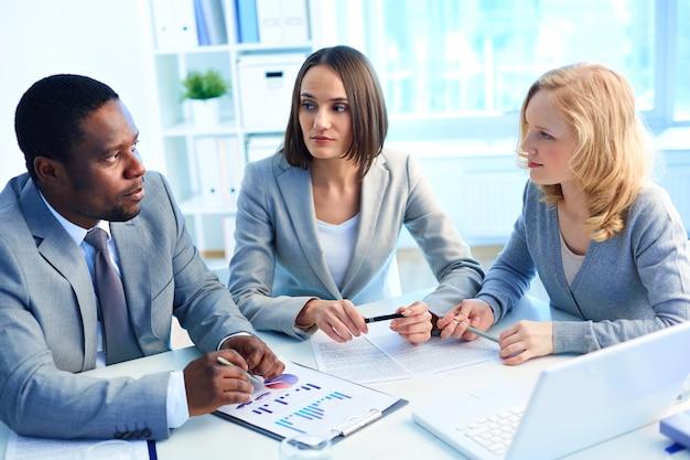 Compañeros de trabajo con documentos estadísticos