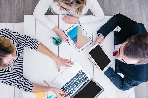 Compañeros de trabajo conversando y usando gadgets en la mesa