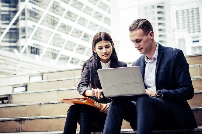 Compañeros de trabajo de negocios discutiendo nuevas ideas y lluvia de ideas en la computadora portátil sentado en la oficina de la escalera