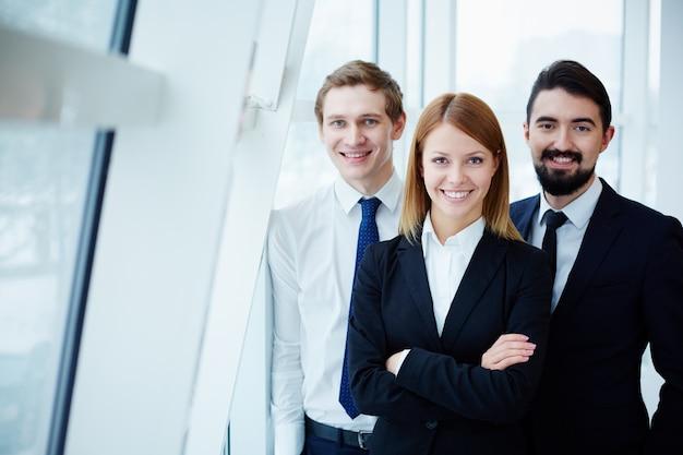 Compañeros de trabajo felices junto a la ventana