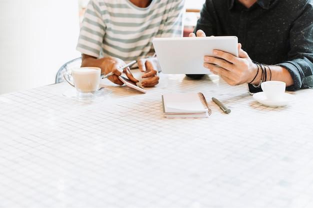 Compañeros discutiendo el trabajo en una mesa con espacio de diseño