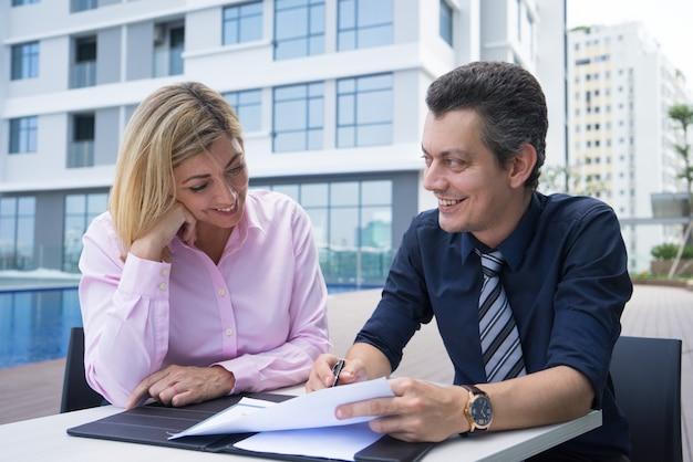 Compañeros emprendedores positivos que elaboran estrategia mientras ven el informe en el café de la ciudad