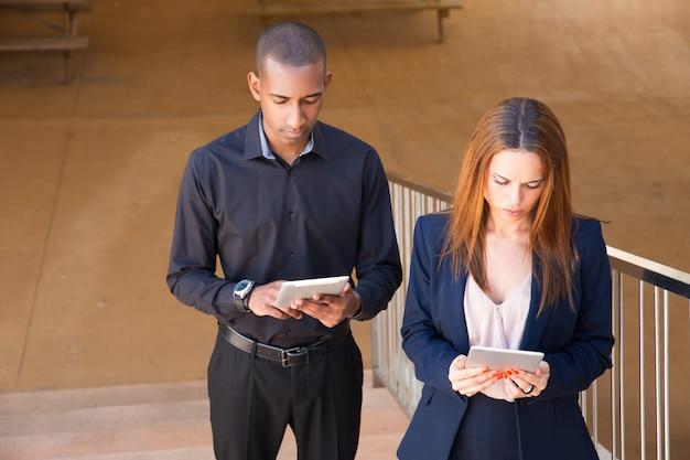Compañeros enfocados que leen noticias en tabletas en escaleras