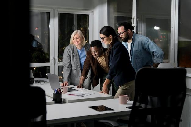 Compañeros de equipo trabajando hasta tarde en la oficina.