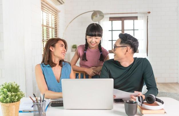 Compañeros de familia asiáticos felices trabajan con ordenador portátil en el interior de la oficina hablando entre sí.