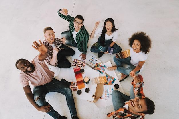 Compañeros felices están sentados en el piso y celebrando