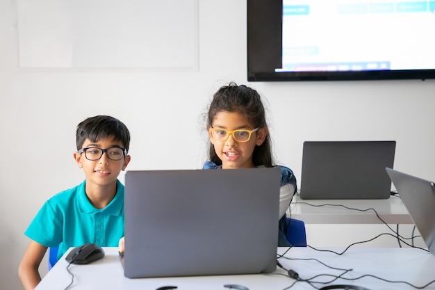 Compañeros felices en vasos sentados a la mesa juntos y usando la computadora portátil en el aula