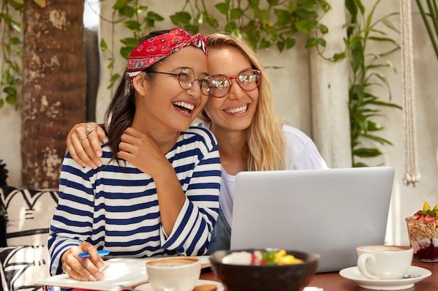 Los compañeros de grupo interraciales escriben información del sitio web de internet, tienen relaciones amistosas