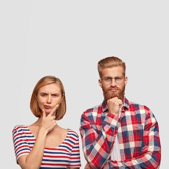 Los compañeros de grupo jóvenes reflexivos intentan encontrar una solución, tienen expresiones inteligentes e inteligentes, sostienen la barbilla, miran con seriedad