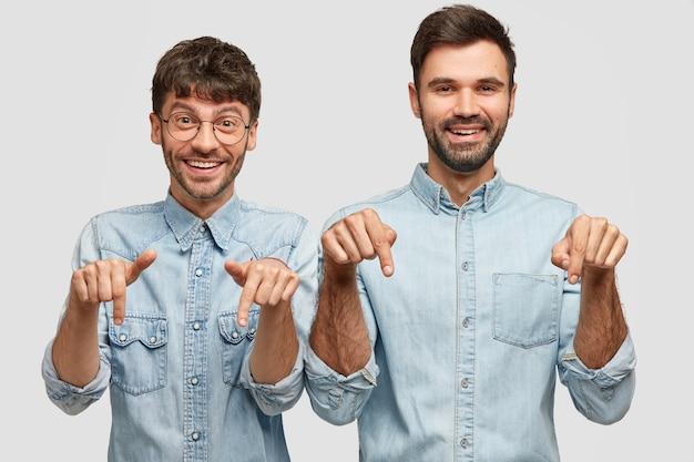 Compañeros de hombre alegre con expresiones positivas, señalar hacia abajo, involucrados en publicidad, vestidos con ropa casual