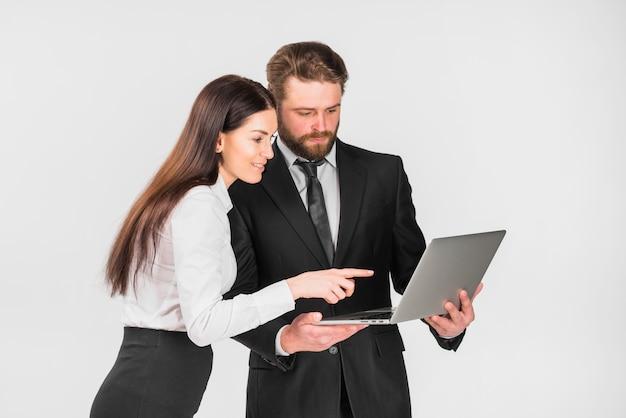 Compañeros hombre y mujer planeando y mirando portátil