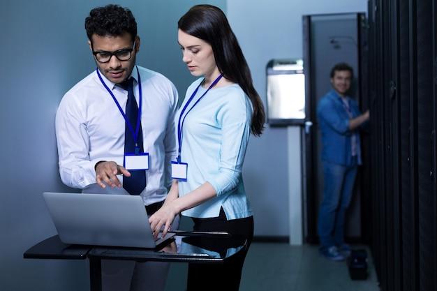 Compañeros jóvenes profesionales serios de pie frente a la computadora portátil y trabajando en ella mientras están en el centro de datos