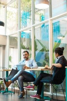 Compañeros multiétnicos confiados que tienen reunión informal en café