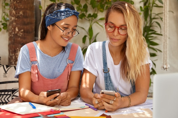 Compañeros multirraciales alegres satisfechos con el trabajo productivo, hablan entre sí