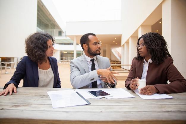 Compañeros de negocios discutiendo informes de proyectos