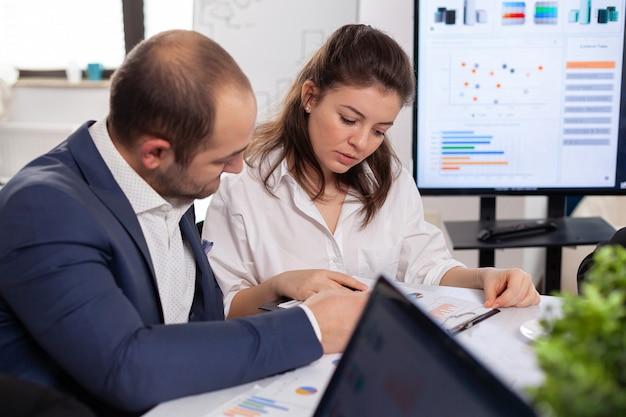 Compañeros de negocios de inicio discutiendo mirar documentos en la junta de la empresa, haciendo una lluvia de ideas, revisando gráficos y tablas en la sala de conferencias