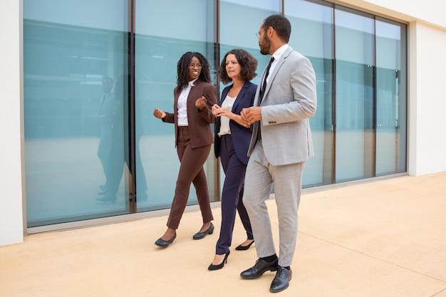 Compañeros de negocios multiétnicos caminando y hablando