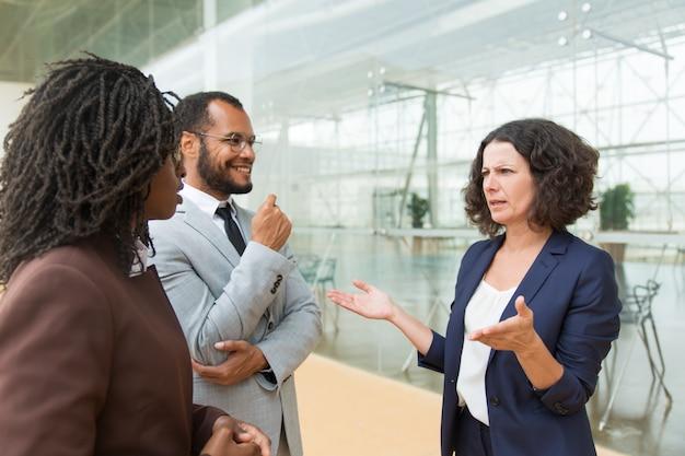 Compañeros de negocios positivos conversando afuera