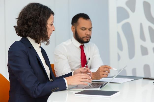Compañeros de negocios serios con computadora y documentos