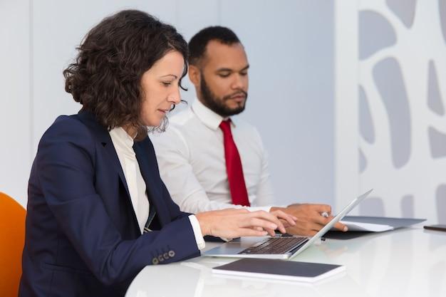 Compañeros de negocios serios que controlan la computadora
