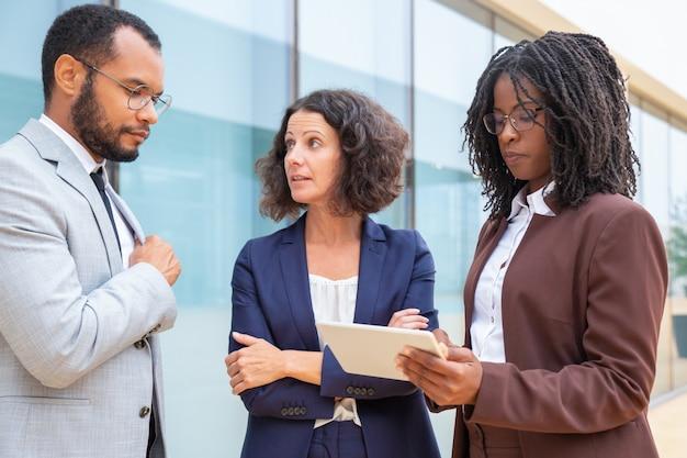 Compañeros de negocios serios con tableta discutiendo proyecto