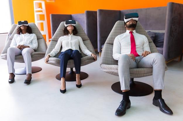 Compañeros de negocios tranquilos que disfrutan de la experiencia de realidad virtual
