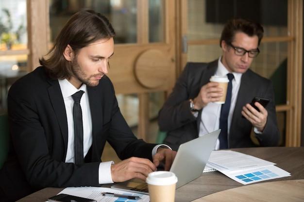 Compañeros ocupados utilizando dispositivos tecnológicos durante el descanso de la empresa