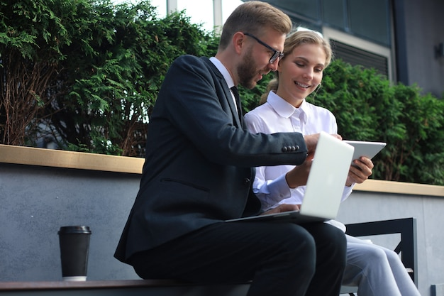 Compañeros de oficina usando la computadora portátil mientras está sentado en un banco al aire libre.
