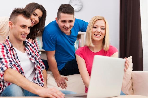 Compañeros de piso usando laptop en salón