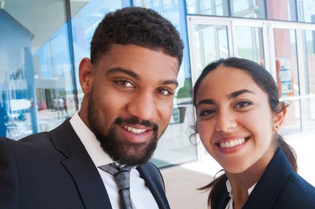 Compañeros positivos que presentan y que toman la foto del selfie al aire libre