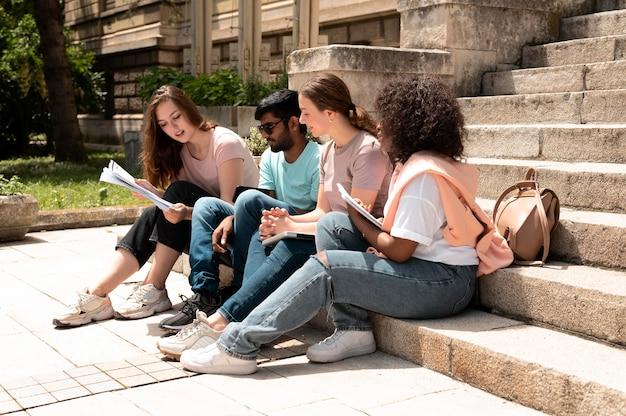 Compañeros que estudian juntos frente a su universidad antes de un examen