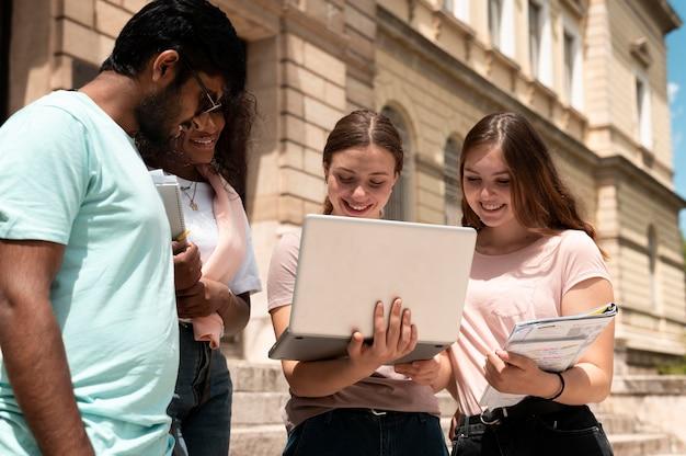 Compañeros que estudian juntos frente a su universidad.