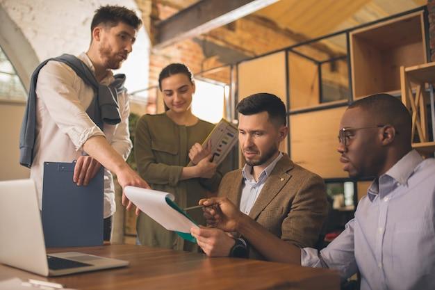 Compañeros que trabajan juntos en la oficina moderna utilizando dispositivos y gadgets durante una reunión creativa