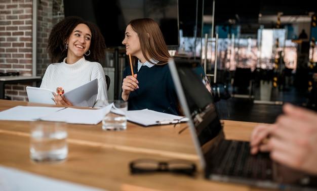 Compañeros sonrientes hablando entre sí durante una reunión