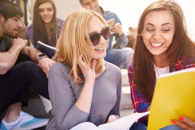 Compañeros sonrientes que tienen un descanso en la universidad