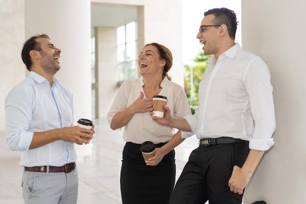 Compañeros de trabajo adultos alegres mediados de risa en el descanso para tomar café