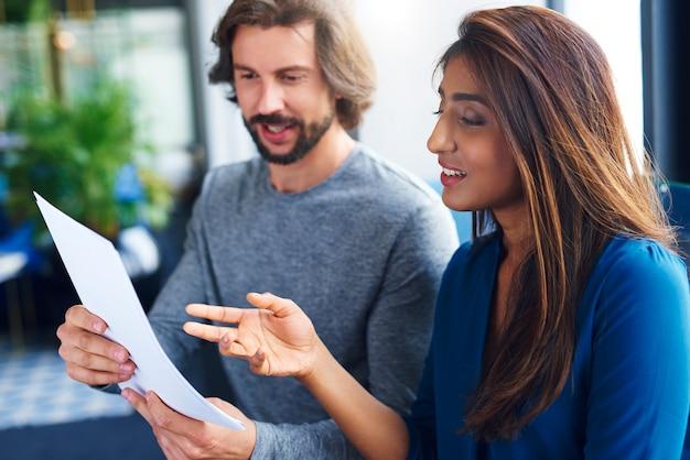 Compañeros de trabajo adultos jóvenes analizando el documento