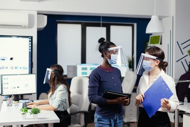 Compañeros de trabajo africanos y caucásicos discutiendo estadísticas en el lugar de trabajo usando mascarilla. equipo empresarial multiétnico que trabaja respetando la distancia social durante la pandemia global con coronavirus.