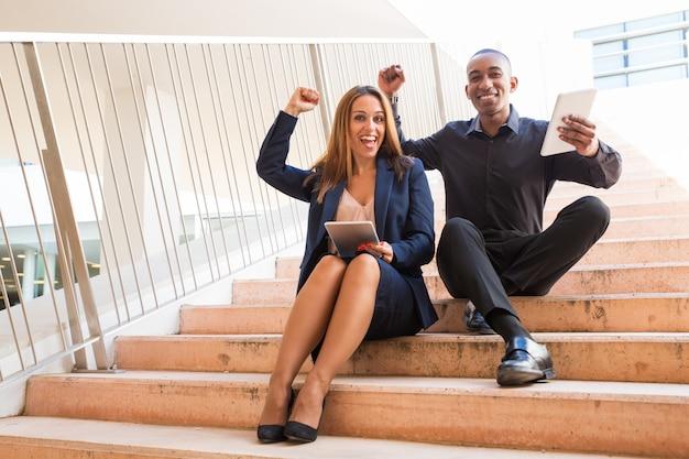 Compañeros de trabajo alegres que sostienen las tabletas y sentado en las escaleras
