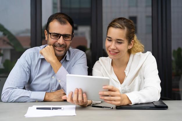 Compañeros de trabajo alegres que tienen video chat