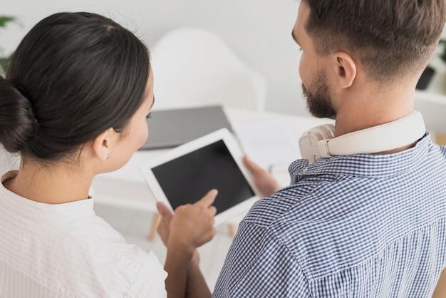 Compañeros de trabajo de alto ángulo mirando tablet