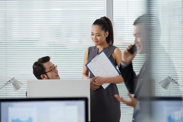 Compañeros de trabajo asiáticos discutiendo algo mientras su colega hablando por teléfono