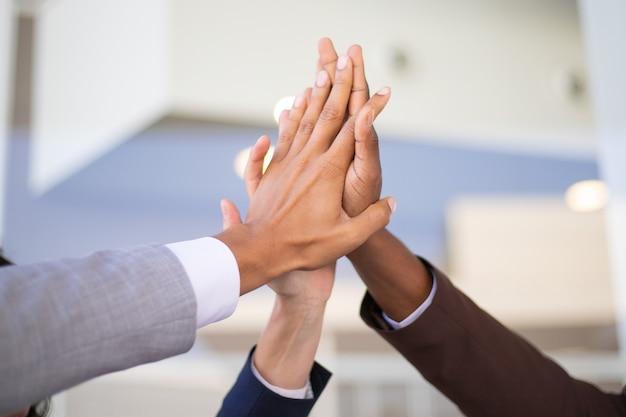 Compañeros de trabajo celebrando el éxito y uniendo manos